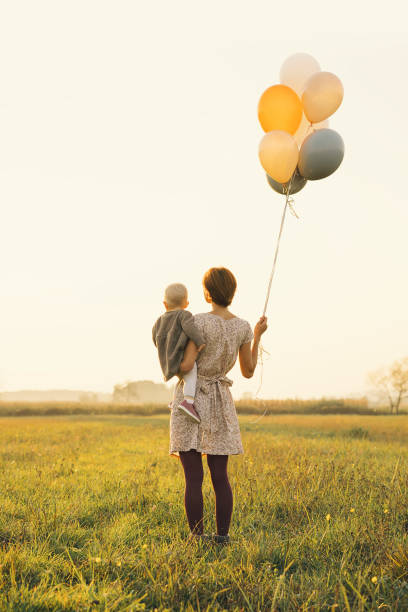 Young mother and baby girl with balloons in sunlight at sunset on picture id1180828477?b=1&k=6&m=1180828477&s=612x612&w=0&h=ktlq3kecuewr2okrq5j7yd88lubnwf umnpwl5nap8i=
