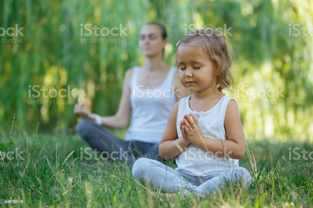 Young mother and cute little daughter meditating in lotus pose together stock photo