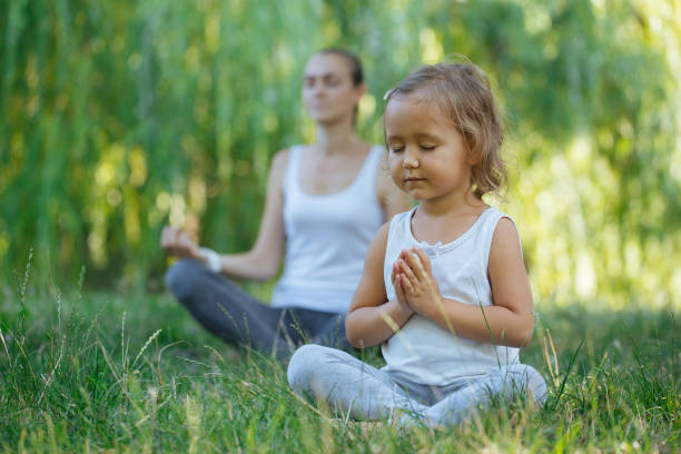 young mother and cute little daughter meditating in lotus pose together - zen like stock pictures, royalty-free photos & images