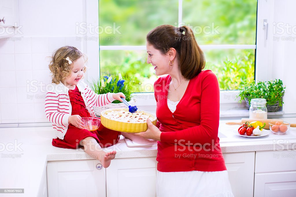 Young mother and daughter baking a pie stock photo