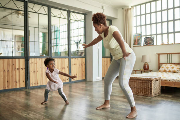 Young Mother and Daughter Doing Dance Exercises At Home stock photo