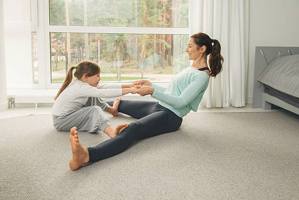 Young mother and daughter doing morning yoga exercise stock photo