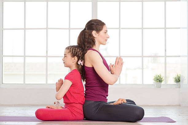 Young mother and daughter doing yoga exercise stock photo