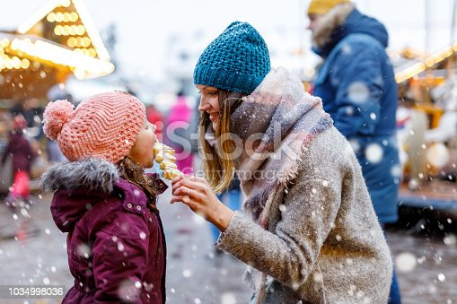 Young mother and daughter eating white chocolate covered fruits on skewer on traditional German Christmas market. Happy girl and woman on traditional family market in Germany, Munich during snowy day