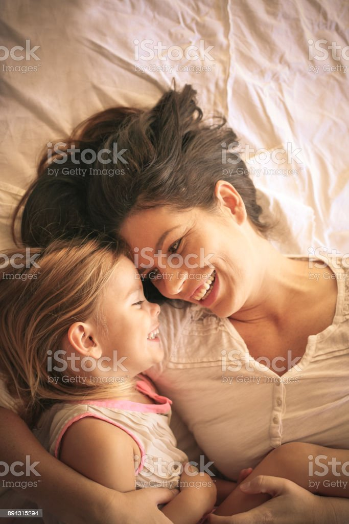 Young  mother and daughter laying in bed together at home. stock photo