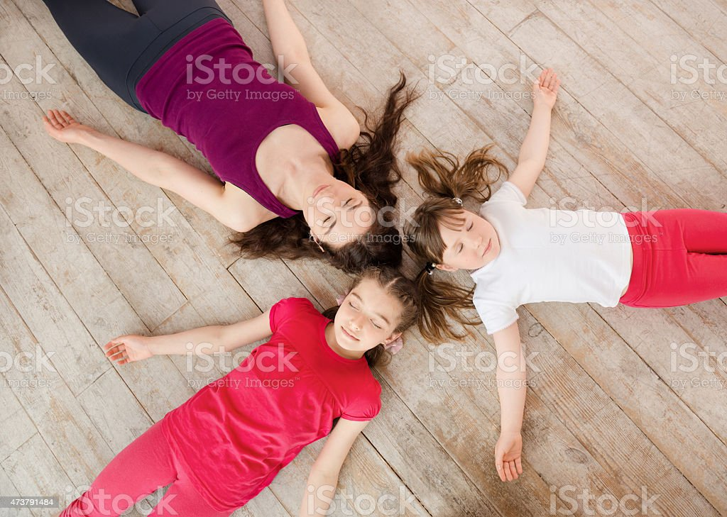 Young mother and daughter lying on the floor stock photo