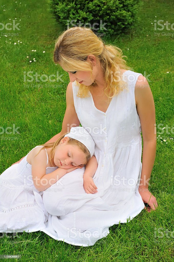 Young mother and daughter resting in meadow royalty-free stock photo