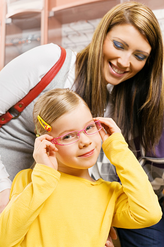 Young Mother And Daughter Shopping For New Glasses Stock Photo - Download Image Now