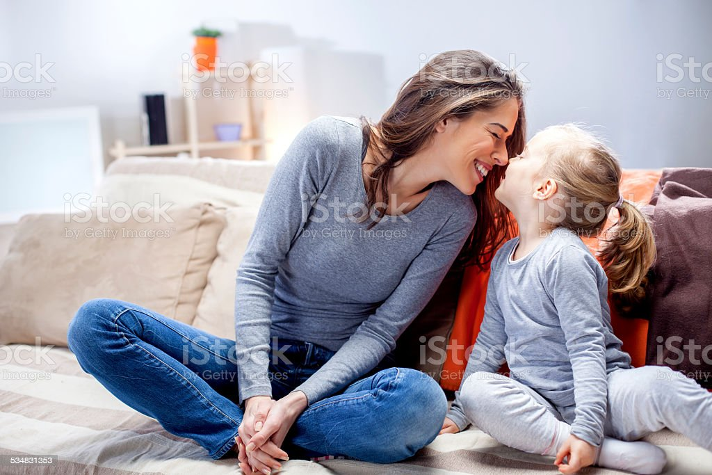 Young mother and daughter sitting on  bed in  living room stock photo
