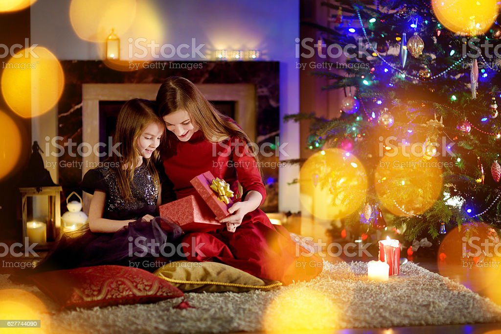Young Mother And Daughter Unwrapping Gifts By Fireplace On Christmas ...