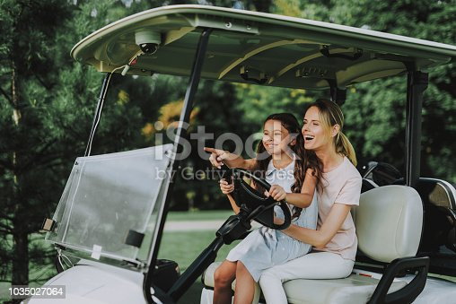 Young Mother and Daughter with Cart on Field. Happy Family. Little Girl. Driver with Car. Healthy Lifestyle Concept. Golf Club. Sports in Summer. Vehicle on Field. Outdoor Fun in Summer.