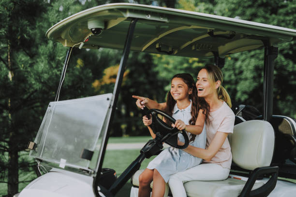 Young Mother and Daughter with Cart on Field. Young Mother and Daughter with Cart on Field. Happy Family. Little Girl. Driver with Car. Healthy Lifestyle Concept. Golf Club. Sports in Summer. Vehicle on Field. Outdoor Fun in Summer. golf cart stock pictures, royalty-free photos & images