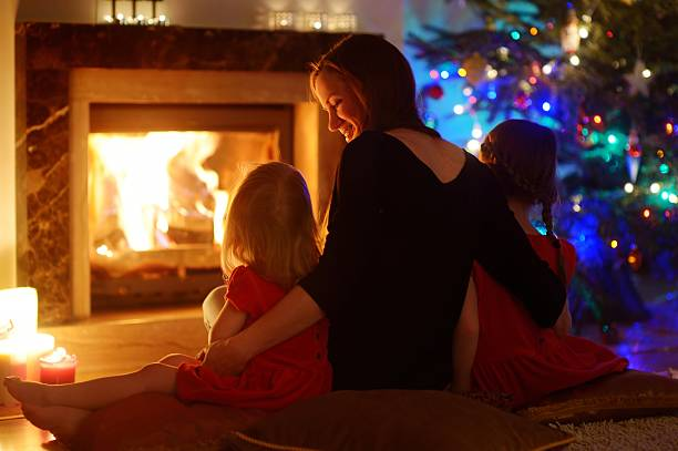 young mother and daughters sitting by a fireplace on christmas - cosy pillows mother child bildbanksfoton och bilder