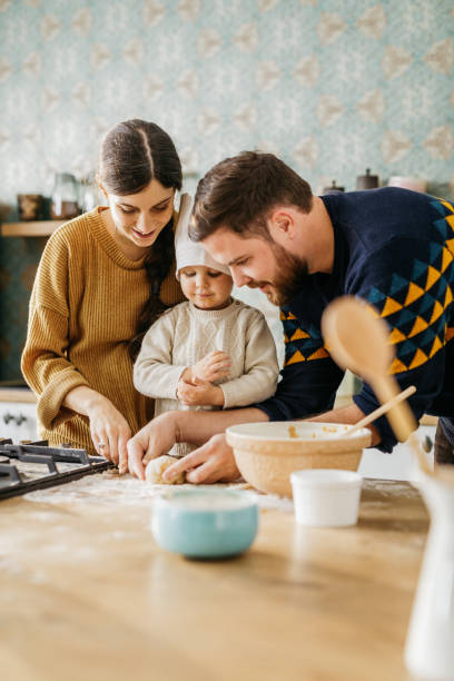 Young mother and father are cooking with their little chef stock photo