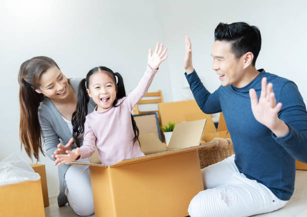 Young Mother and Father enjoying and playing with their Daughter and her sitting in cardboard. stock photo
