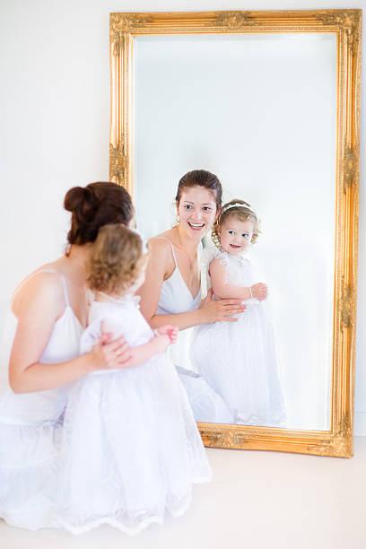 junge mutter und ihre entzückende kleine tochter nächste große spiegel - hochzeitsspiele eltern stock-fotos und bilder