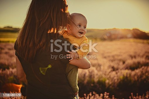 Happy young mother and her baby son having fun in the lavander field on the beautiful summer day.