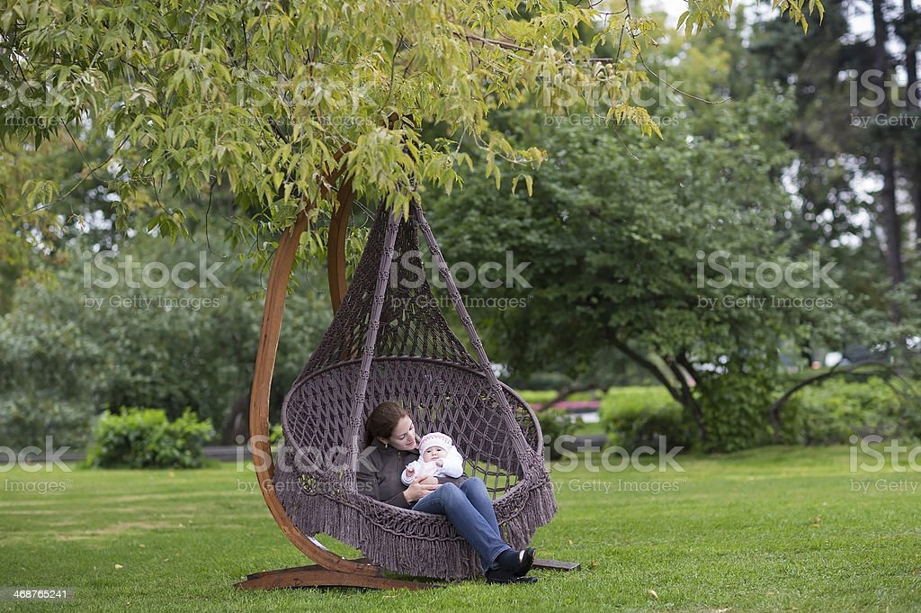 Young mother and her baby daughter relaxing in a hammock royalty-free stock photo