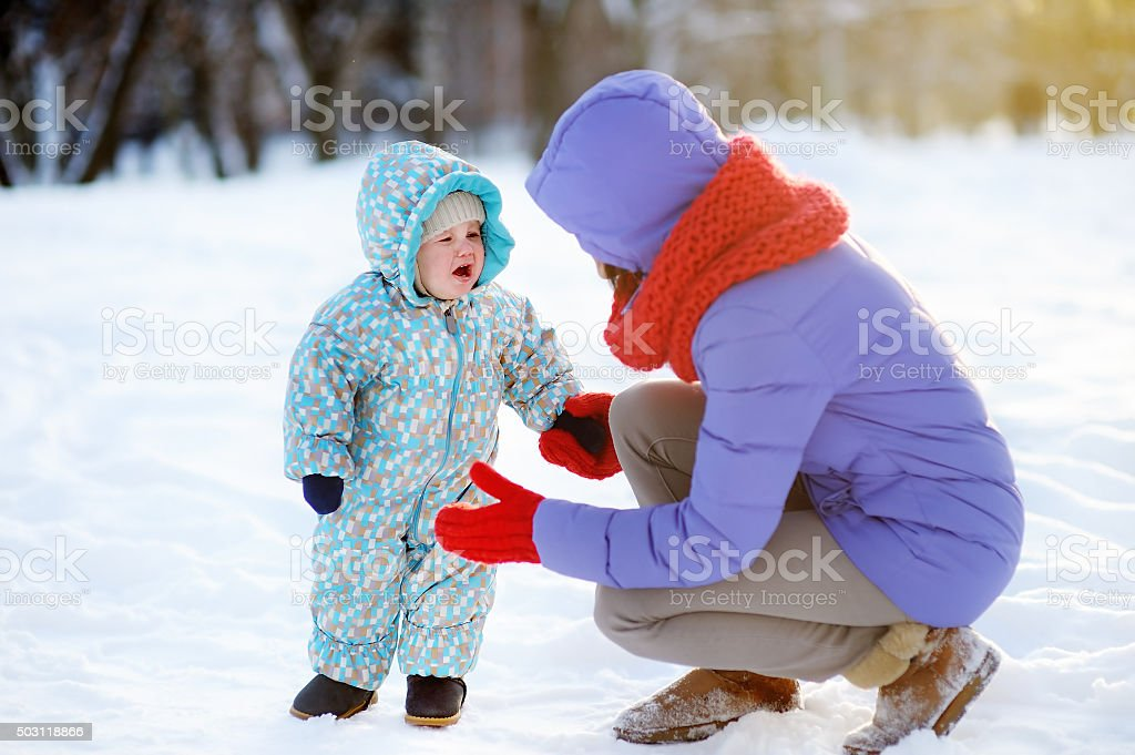 Young mother and her crying toddler child stock photo