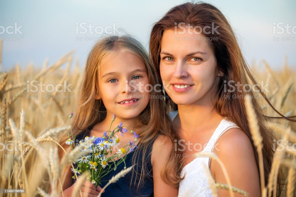 Young Mother And Her Daughter On Golden Wheat Field At