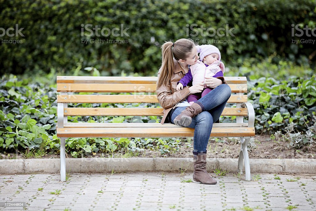 Young mother and her daughter sitting on a bench royalty-free stock photo