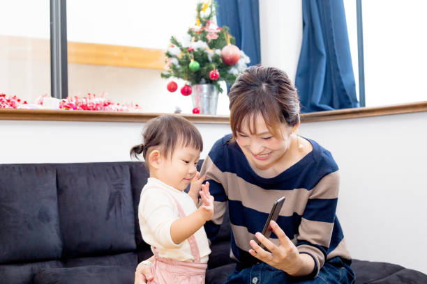 Young mother and her daughter watching something on a smart phone Casual baby playing happy with a smartphone only japanese stock pictures, royalty-free photos & images