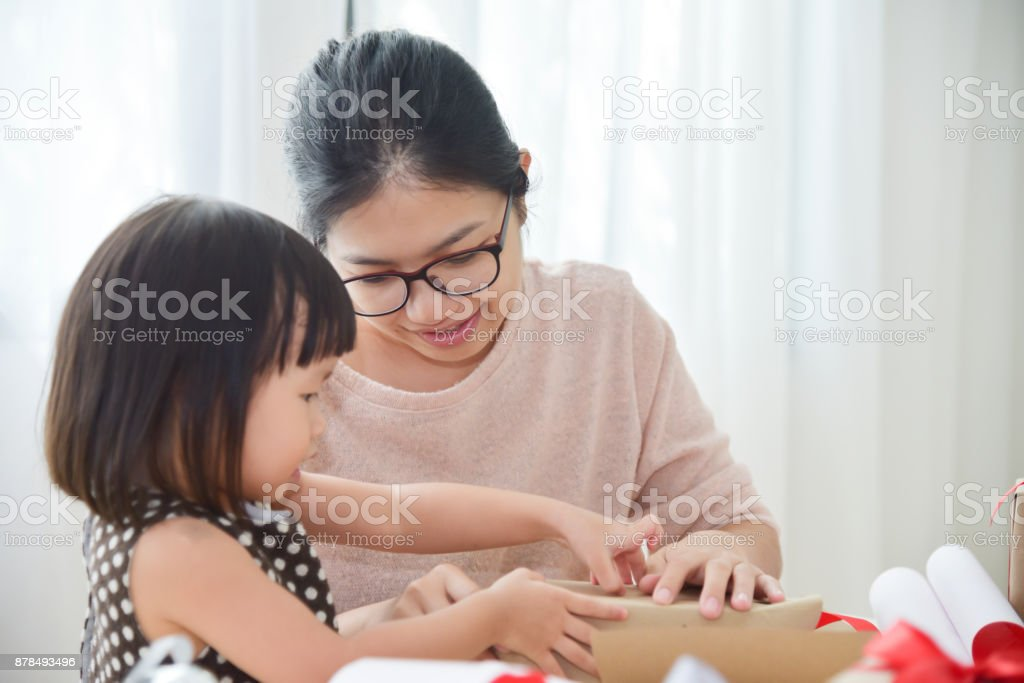 Young Mother And Her Daughter Wrapping A Gift Box Royalty Free Stock Photo