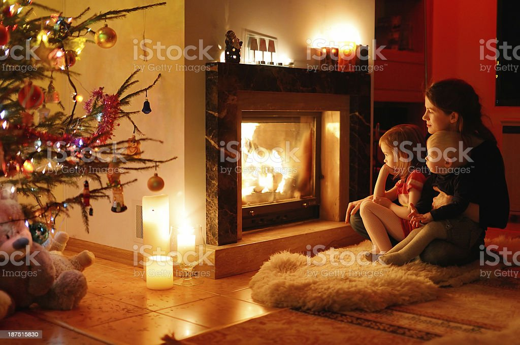 Young mother and her daughters by a fireplace stock photo