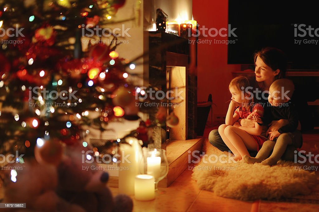 Young mother and her daughters by a fireplace royalty-free stock photo