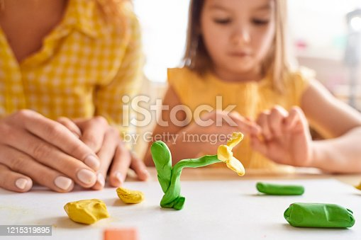 istock Young mother and her junior daughter playing with plasticine 1215319895