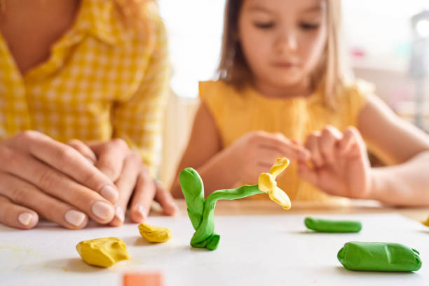 Young mother and her junior daughter playing with plasticine Selective focus on plasticine flower against blurred background with young mother and her junior daughter spending day together, playing at home clay stock pictures, royalty-free photos & images