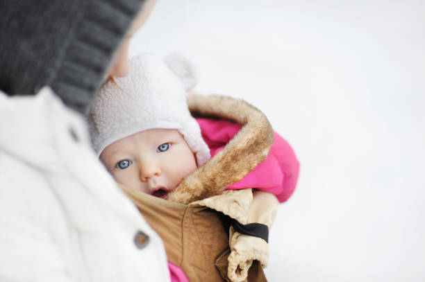 Young mother and her little baby in a carrier stock photo