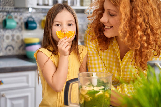 Young mother and her little child girl standing on kitchen together stock photo