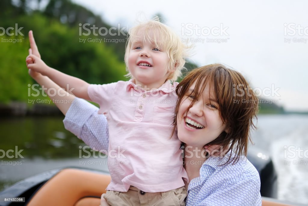 Young mother and her little son enjoy boating stock photo
