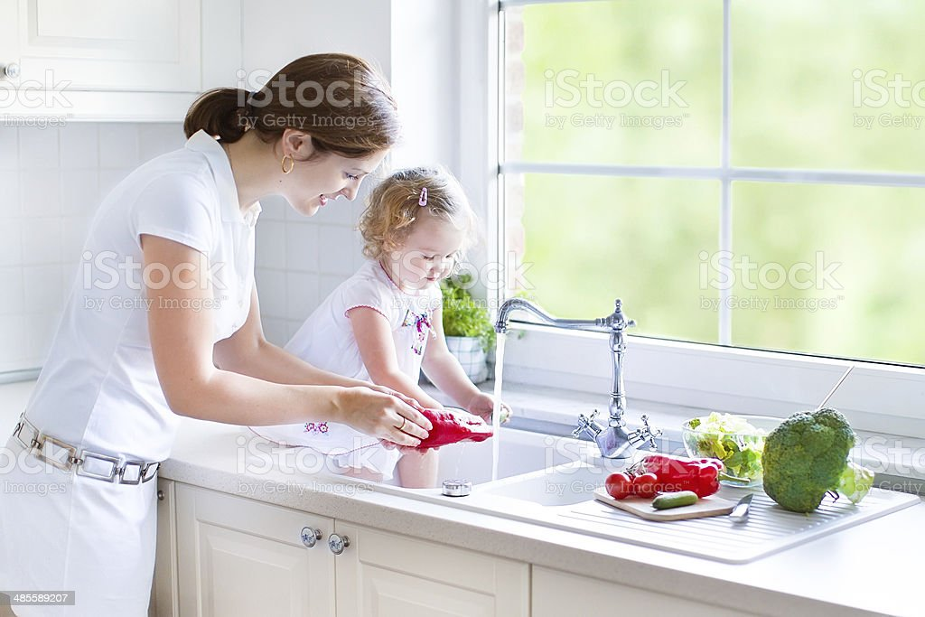Young mother and her toddler daughter washing vegetables for lunch stock photo