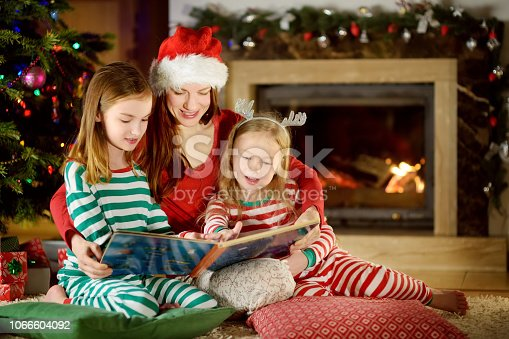 istock Young mother and her two little daughters reading a book by a Christmas tree in living room in winter 1066604092
