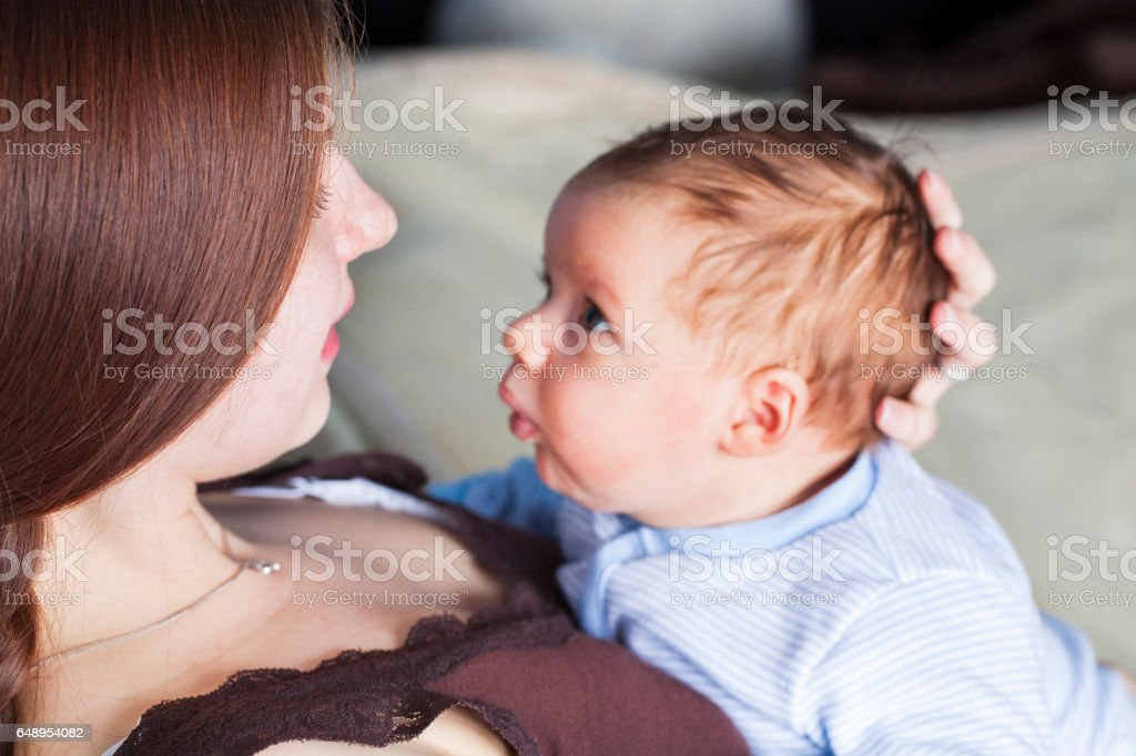 Young mother and little baby boy resting on her chest stock photo