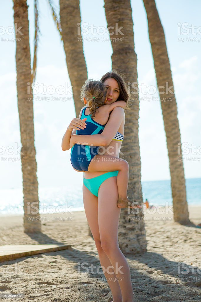 Young mother and little daughter embracing each other on beach stock photo