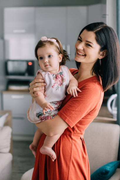 Young mother and little daughter together in kitchen at home stock photo