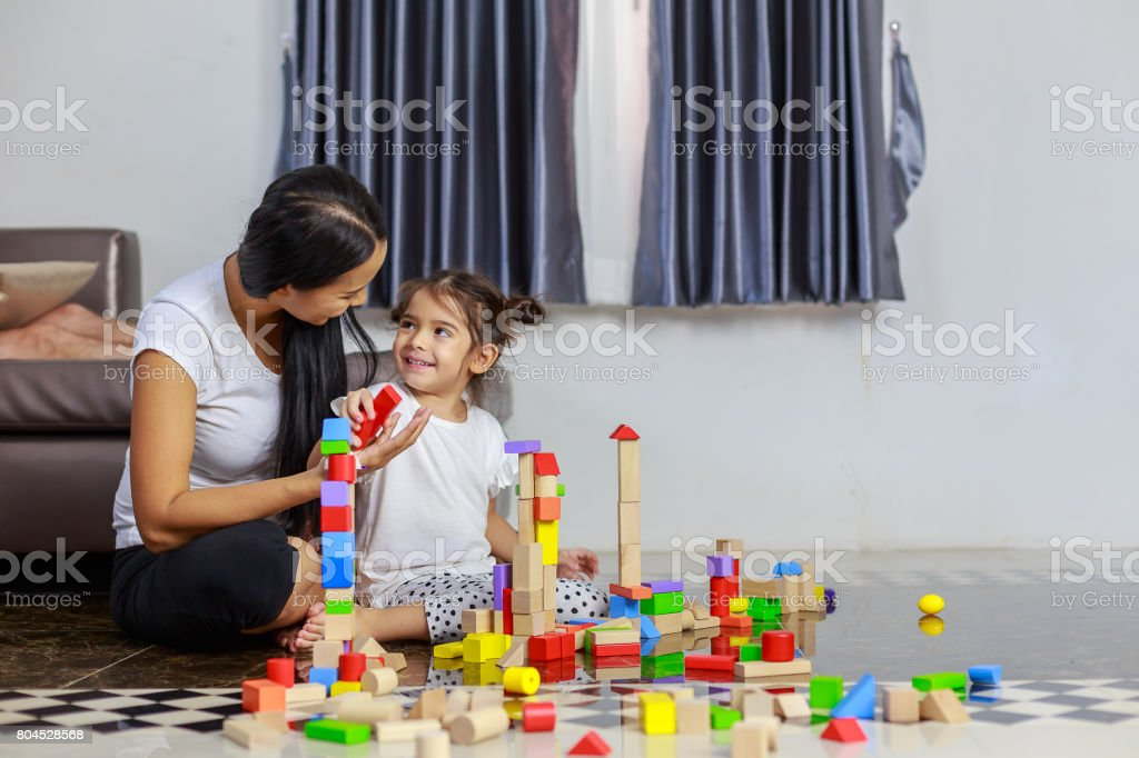 Young mother and little girl play wooden toys blocks on the floor, building towers at home stock photo