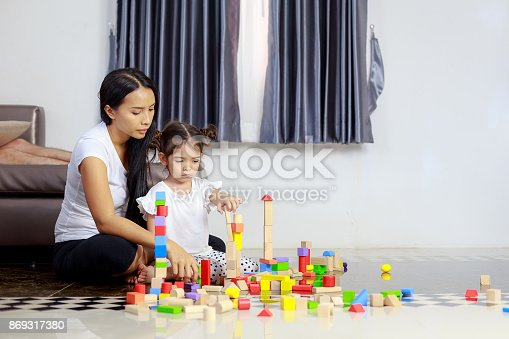 470874196istockphoto Young mother and little girl play wooden toys blocks on the floor, building towers at home 869317380