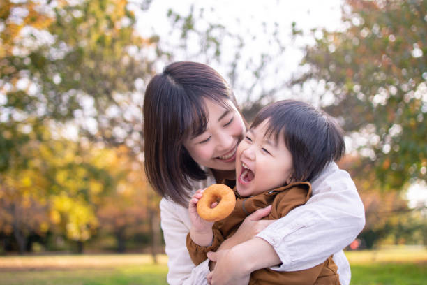 Young mother and son eating doughnut in public park with full of fun stock photo