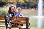 若い母親と息子が公共の公園でカメラを見て