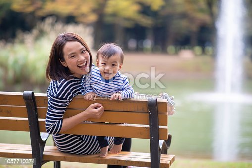 Young mother and son looking at camera in public park