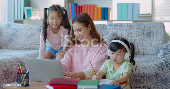 Asian young mother teaching eldest daughter with laptop, youngest daughter wearing headphone and writing on paper nearby, work at home and single mom concept