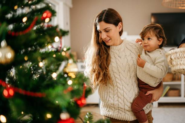 Young mother and their son decorating christmas tree stock photo