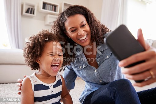 Young mother and toddler daughter taking selfie at home