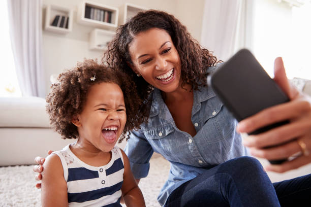 young mother and toddler daughter taking selfie at home - selfie foto e immagini stock