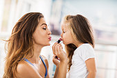 Young mother applying lipstick on her little girl who is puckering.