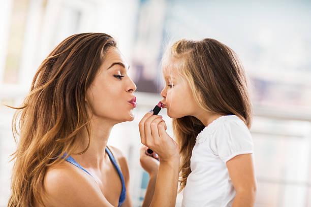 Junge Mutter anwenden Lippenstift auf ihre Tochter. – Foto